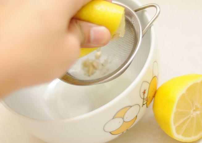 Лимон остудить, разрезать на две части и отжать в отдельную чашку, устранив косточки